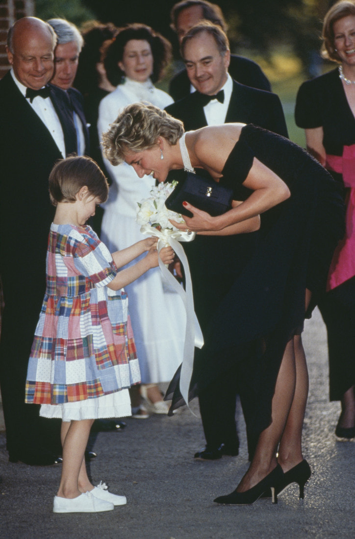 Princess Diana (1961 - 1997) receives a bouquet from a young girl, as she arrives for a gala event at the Serpentine Gallery, London, 29th June 1994. The princess is wearing a black gown by Christina Stambolian. (Photo by Tim Graham/Getty Images)